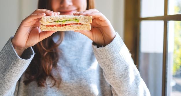 Uma linda mulher segurando e mostrando um pedaço de sanduíche de trigo integral para comer