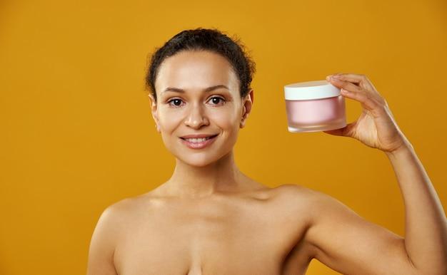 Uma linda mulher segurando um frasco de hidratante perto do rosto isolado em um fundo amarelo