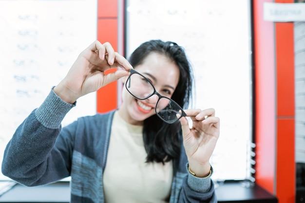 Uma linda mulher segurando uma amostra de óculos em uma clínica de olhos contra o fundo de uma vitrine