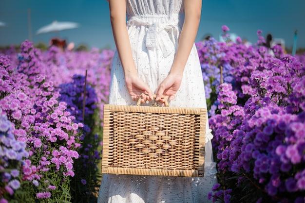 Uma linda mulher segurando uma bolsa de vime no jardim de flores roxas