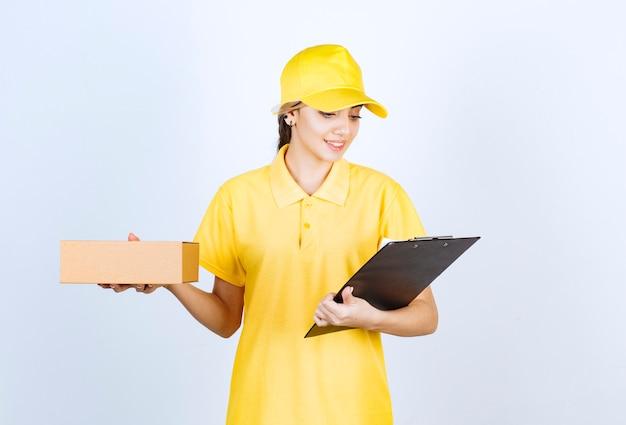 Uma linda mulher segurando uma caixa de papel artesanal em branco marrom com uma pasta.