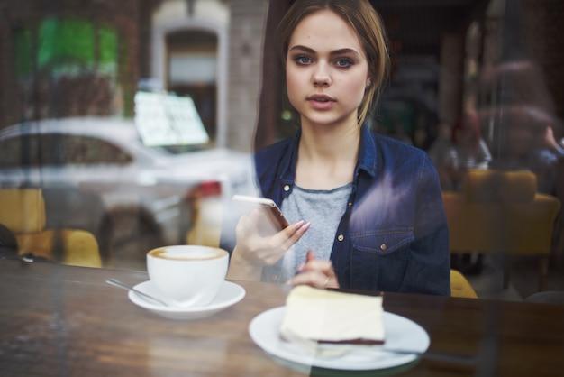 Uma linda mulher sentada à mesa em um café com ar pensativo