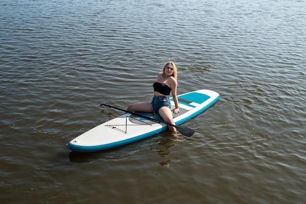 Uma linda mulher sentada e relaxando no supboard, horário de verão