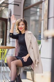 Uma linda mulher sentada em um refeitório ao ar livre esperando por amigos