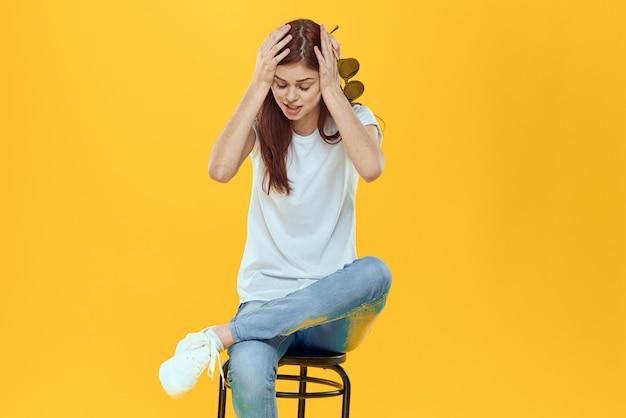 Uma linda mulher sentada em uma cadeira roupas da moda, estilo de vida, fundo amarelo