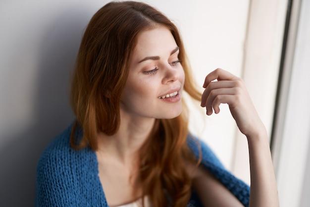 Uma linda mulher sentada no parapeito da janela com uma manta azul pela manhã
