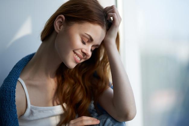Uma linda mulher sentada perto da janela com um estilo de vida xadrez azul