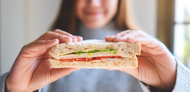 Uma linda mulher sorridente segurando um pedaço de sanduíche de trigo integral para comer