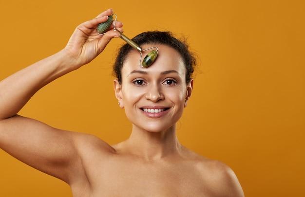 Uma linda mulher sorrindo e massageando a testa com rolo de jade isolado em backgroung amarelo