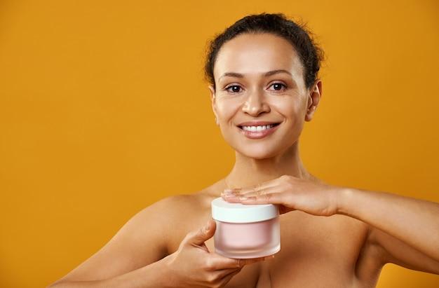 Uma linda mulher sorrindo e segurando um frasco de hidratante isolado em um fundo amarelo