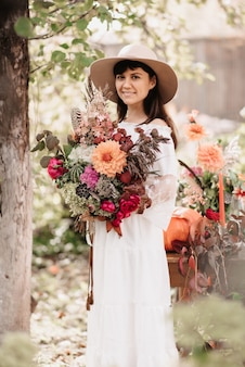 Uma linda mulher tem um buquê de flores e ervas nas mãos. humor romântico