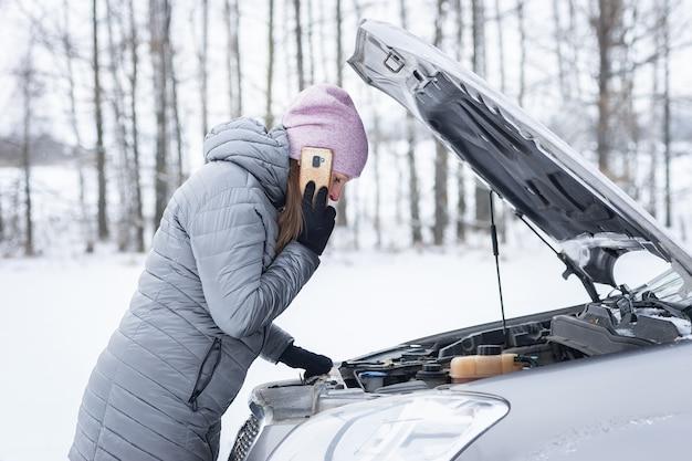 Uma linda mulher tensa fica na estrada e espera ajuda ao lado de um carro quebrado com o capô aberto