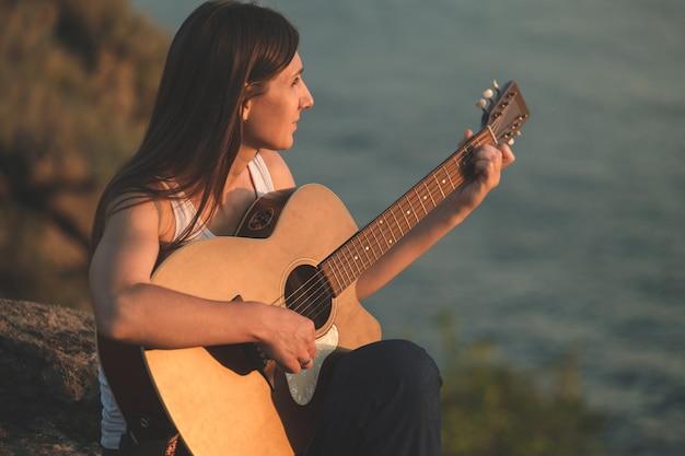 Uma linda mulher tocando violão sentada na rocha. menina bonita praticando música
