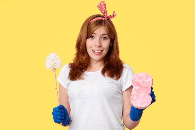 Uma linda mulher trabalha no serviço de limpeza, faz limpeza geral, segura escova e esponja, veste camiseta branca e luvas de borracha, olha com expressões felizes, recebe elogios por um bom trabalho diligente