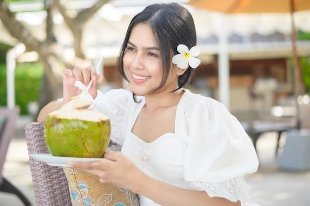 Uma linda mulher turista com uma flor branca no cabelo, bebendo coco, sentada em uma espreguiçadeira durante as férias de verão