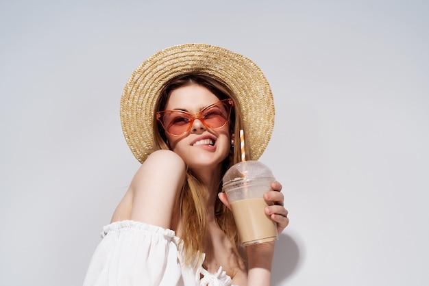 Uma linda mulher, um copo com uma bebida na mão, moda vista recortada