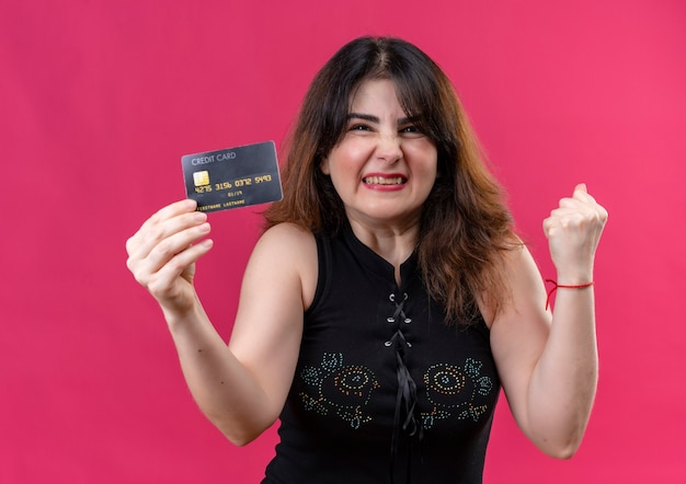Uma linda mulher usando blusa preta e feliz segurando o cartão