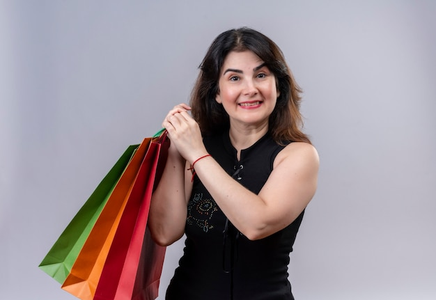 Uma linda mulher usando blusa preta e parecendo feliz em fazer compras segurando sacolas