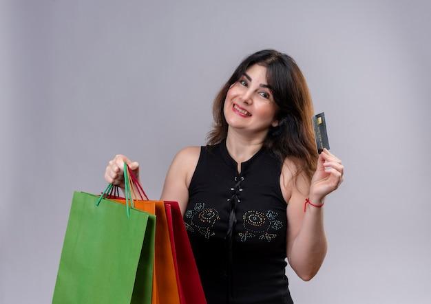 Uma linda mulher usando blusa preta olhando feliz para fazer compras com um cartão de crédito segurando sacolas de compras