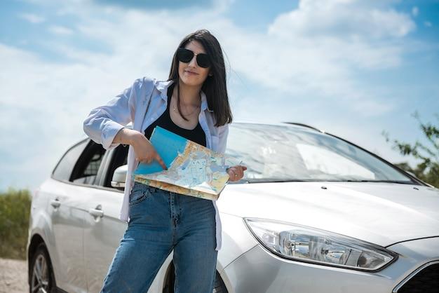 Uma linda mulher vê o mapa perto de um carro na estrada