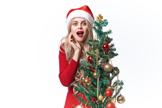 Uma linda mulher vestida de papai noel, árvore de natal, brinquedos, decoração festiva