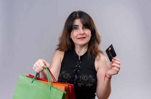 Uma linda mulher vestindo blusa preta alegrou-se segurando um cartão de crédito e sacolas de compras