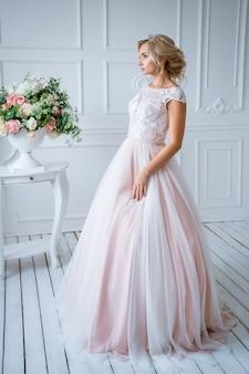 Uma linda noiva com cabelos e maquiagem fica em um delicado vestido de noiva rosa em uma decoração clara com flores