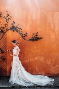 Uma linda noiva com traços agradáveis em um vestido de noiva é fotografada na provença. retrato da noiva na frança.