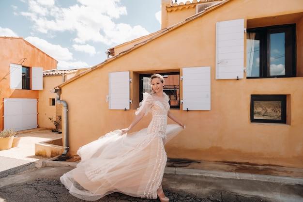 Uma linda noiva com traços agradáveis em um vestido de noiva é fotografada na provença.
