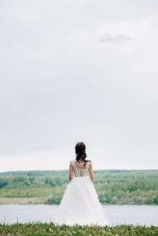 Uma linda noiva se levanta e descansa no contexto da natureza. retrato de casamento de uma linda noiva.