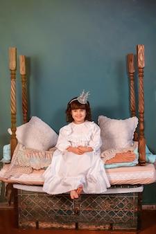 Uma linda princesinha está sentada em uma cama de madeira vintage