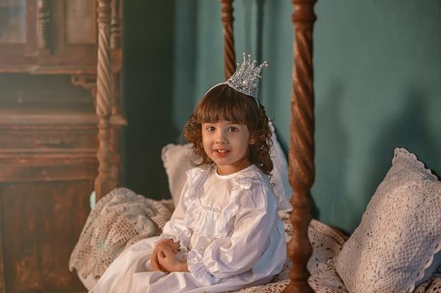 Uma linda princesinha sentada em um vestido vintage em uma cama de madeira