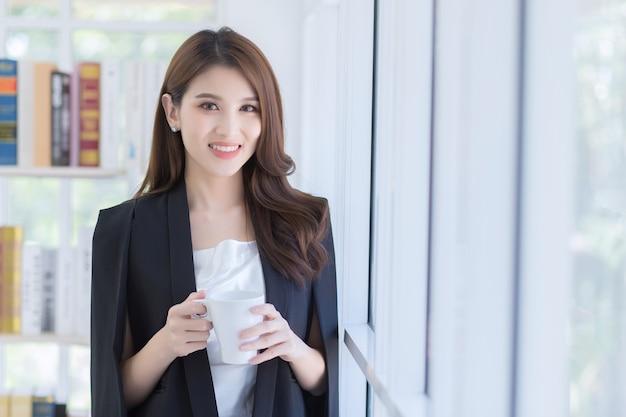Uma linda senhora de escritório segurando uma xícara de café perto da janela. felizmente no local de trabalho