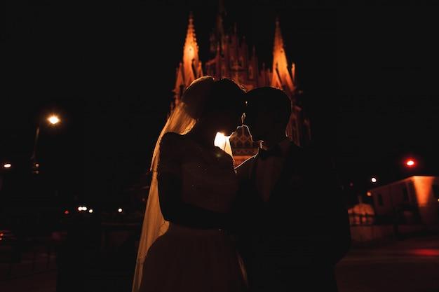 Uma linha clara de luz descreve a silhueta do jovem casal. atrás deles está a arquitetura de cracóvia.