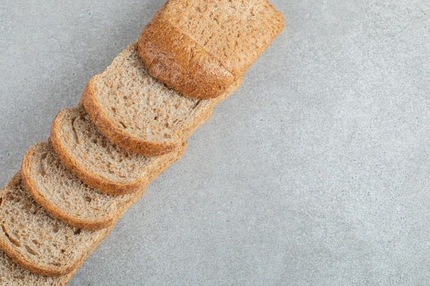 Uma linha de fatias de pão integral em um fundo cinza.