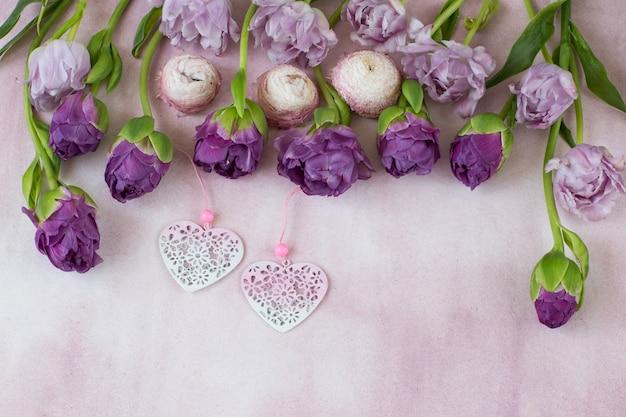Uma linha são tulipas roxas e dois corações cor de rosa