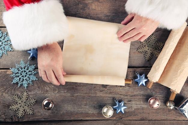 Uma lista de desejos de natal no papai noel com as mãos na mesa de madeira