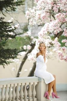 Uma loira bonita senta-se em uma cerca decorativa branca