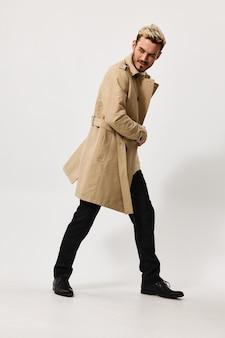 Uma loira fofa de paletó e calça em um fundo claro caminha para o lado em pleno crescimento