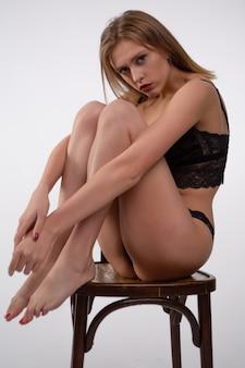 Uma loira linda em um biquíni de renda preta está sentada em uma cadeira.