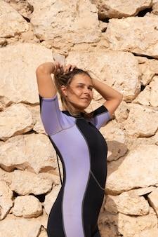 Uma loira, linda, garota com uma roupa de mergulho posando em um dia ensolarado, na costa no contexto de uma parede de pedra.