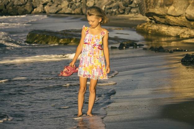 Uma loira sonhadora em um lindo vestido caminha ao longo da costa