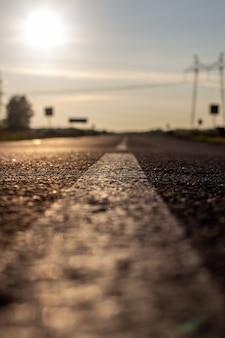 Uma longa faixa branca, como um marcador de estrada. uma estrada na distância entre campos e florestas.