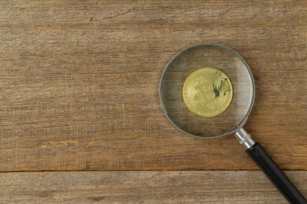 Uma lupa e bitcoin em uma placa de madeira surrada. Foto Premium