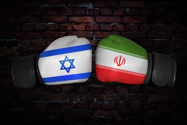 Uma luta de boxe. confronto entre o irã e israel. bandeiras nacionais iranianas e israelenses em luvas de boxe. competição esportiva entre os dois países. conceito de conflito de política externa.