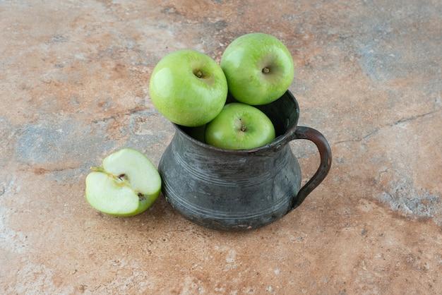 Uma maçã fresca com uma xícara antiga na mesa de mármore.