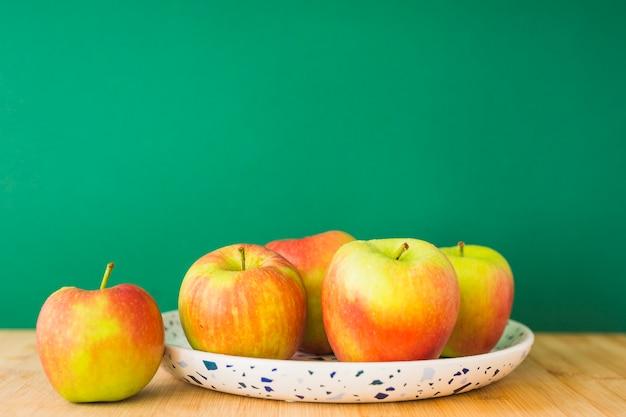 Uma maçã orgânica na placa sobre a mesa de madeira contra o fundo verde