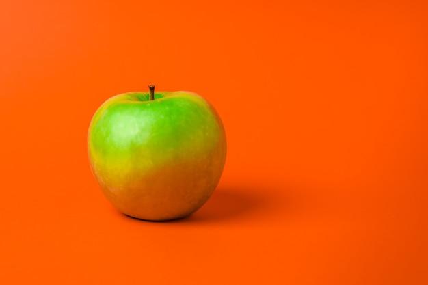 Uma maçã verde em um fundo laranja. minimalismo e espaço de cópia