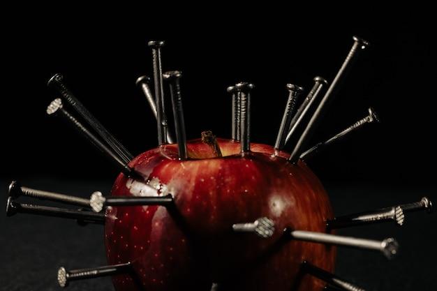 Uma maçã vermelha e unhas nela