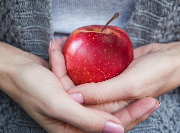 Uma maçã vermelha madura e suculenta nas mãos de mulheres